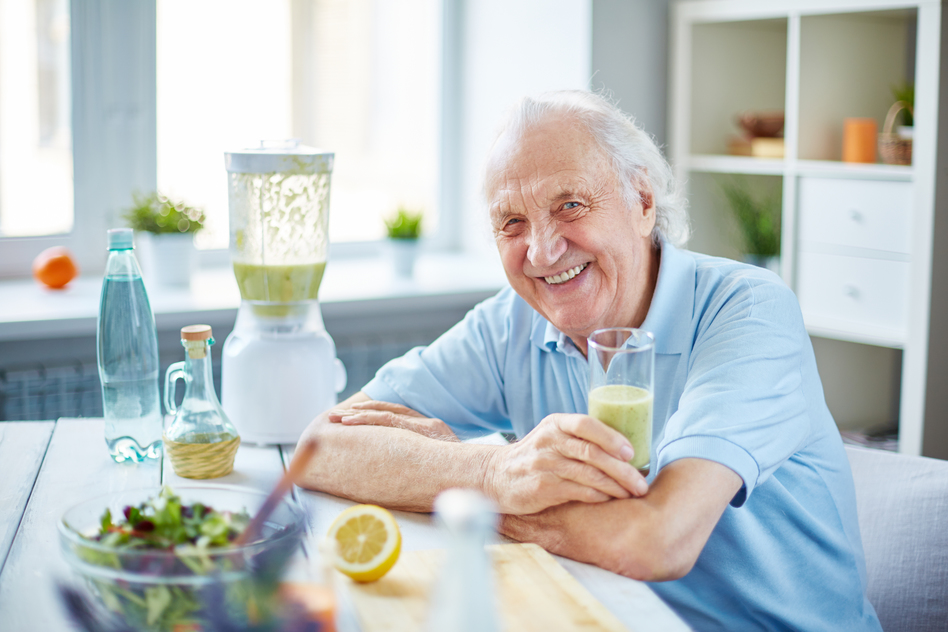 Senior man with glass of smoothie